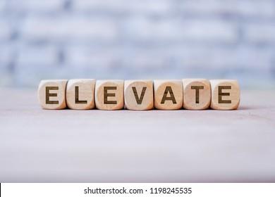 Elevate word written on wood block