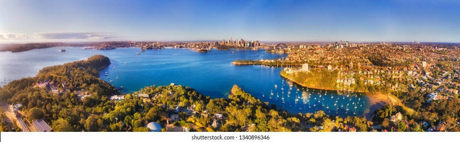 Elevated aerial view over Sydney Harbour from across Mosman and lower north shore suburbs towards city CBD landmarks and waterfront.