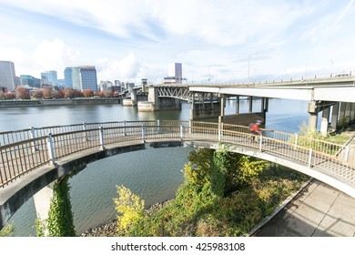elevated bridge near water with cityscape and skyline of portland
