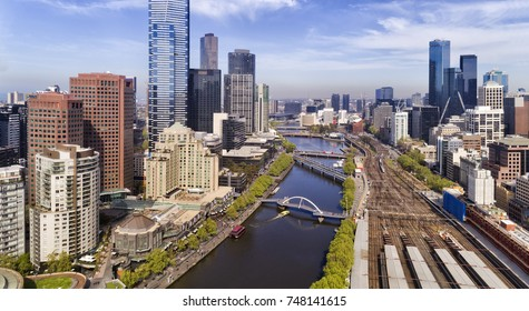 Elevated close-up view inside Melbourne city CBD over Yarra river waters and Flinders station railway platforms between suburbs of high-rise buildings.