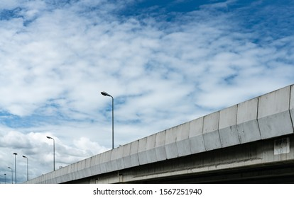 Elevated concrete highway and street lamp pole. Overpass concrete road. Road flyover. Modern motorway. Transportation infrastructure. Concrete bridge engineering construction. Bridge architecture.