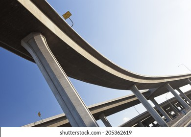 Elevated highway interchange structure, curved winding road under clear blue sky