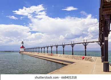 An elevated metal catwalk leads to the East Pierhead Lighthouse at Michigan City, Indiana on a partly cloudy summer afternoon.
