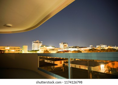 Elevated night view of Bibione, Venice, Veneto, Italy, a popular coastal resort viewed from a covered balcony looking out over rooftops at illuminated hotels on the skyline