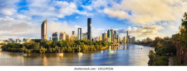 Elevated panorama of Brisbane city CBD surrounded by waters of Brisbane river from Cliffs park in soft morning light after rain.