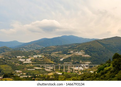 Elevated panoramic view of the Armea Valley in  the Riviera of Flowers with the typical glasshouses for the floriculture and the elevated A10 highway that connect Genoa to Ventimiglia, Imperia, Italy