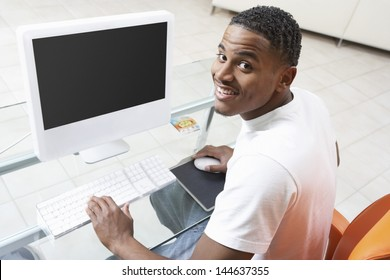 Elevated portrait view of a smiling young man sitting at computer