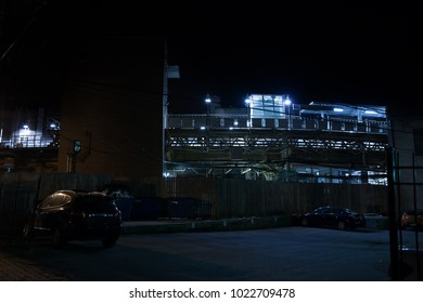 Elevated urban subway bridge and train station next to a dark eerie city alley with cars at night.
