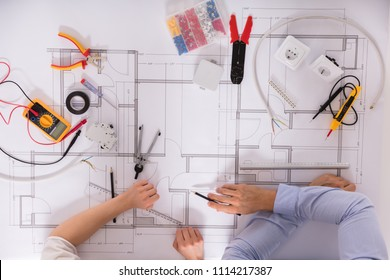 Elevated View Of Architect's Hand And Various Work Tools On Blueprint