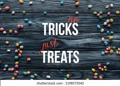 """elevated view of arranged colorful delicious candies on wooden background  with """"no tricks just treats"""" lettering"""