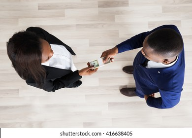Elevated View Of Business Man And Woman Exchanging Money
