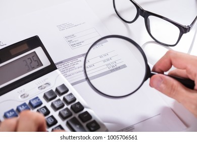 Elevated View Of Businessman Hand Examining Invoice With Magnifying Glass And Calculator In Office