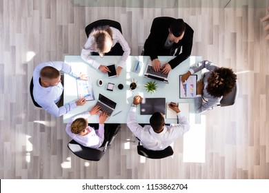 Elevated View Of Businesspeople Working On Graphs In Office