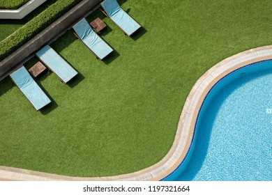Elevated view of close up outdoor swimming pool and pool chairs with clear clean water
