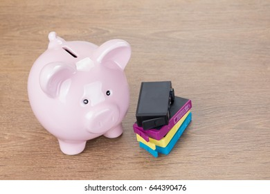 Elevated view of colorful printer cartridges next to piggy bank on wooden background