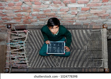 Elevated view of elementary age cheerful School girl of Indian Ethnicity sitting  on cot holding chalkboard wearing school uniform. She is looking up to the camera while sitting on the bed