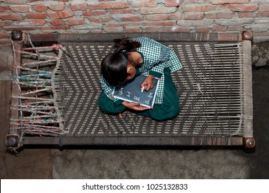 Elevated view of elementary age schoolgirl writing something on chalkboard.