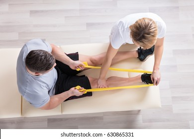 Elevated View Of A Female Physiotherapist Giving Exercise Treatment To Man