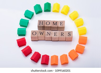 Elevated View Of Homeowner Association Wooden Blocks Surrounded With Multicolored House Models