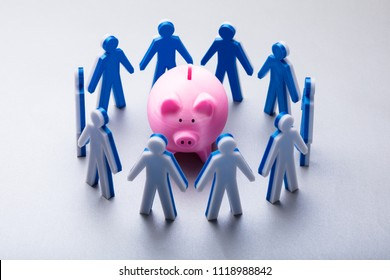 Elevated View Of Human Figures Surrounding Pink Piggybank On White Background