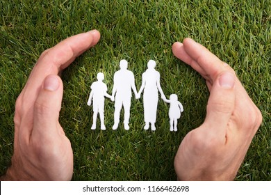 Elevated View Of A Human Hand Protecting Family Paper Cut Out On Green Grass