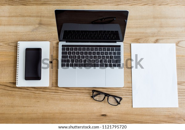 elevated view of laptop, smartphone and notebook on table in business office