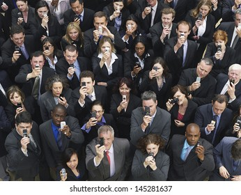 Elevated view of large group of business people taking photographs with mobile phones