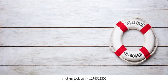 Elevated View Of Lifebuoy With Welcome Aboard Text On Wooden Plank
