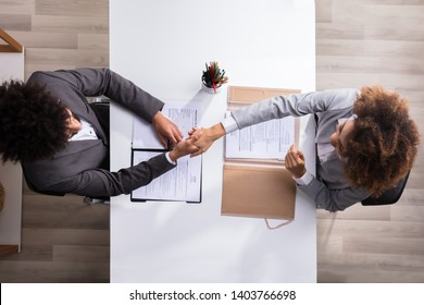 Elevated View Of A Male Manager Shaking Hands With Female Applicant At Workplace