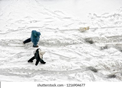 Elevated view of man and woman couple walking with dog on frozen snow covered street in winter