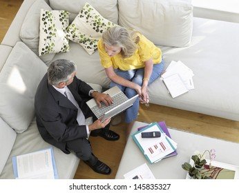 Elevated view of a mature woman sitting on sofa with financial advisor