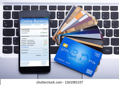 An Elevated View Of Mobilephone With Online Banking App And Credit Cards On Laptop Keypad