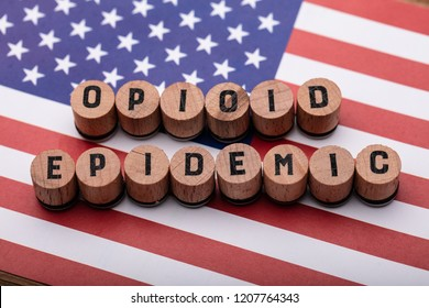 Elevated View Of Opioid Epidemic Text On Wooden Cork Over American Flag