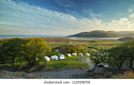 Elevated view over coastal campsite on hill slope with scenic views over Barmouth estuary at sunrise