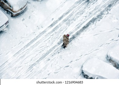 Elevated view of people walking during snow on frozen street with covered parked cars