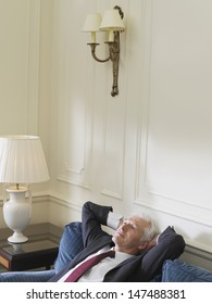 Elevated view of a serious middle aged businessman leaning back with hands behind head on sofa