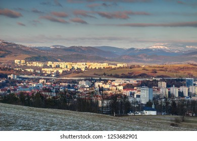 Elevated view of socialist era tower blocks and houses in outskirts of Banska Bystrica with snow-capped Nizke Tatry mountain range in winter sunlight from Urpin hill Slovakia Central / Eastern Europe