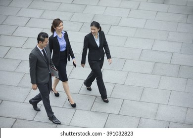 Elevated view of three Chinese Business colleagues walking outdoors. Group of 3 Asian business men and women.