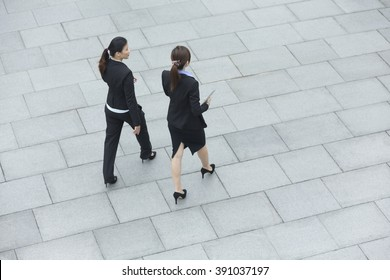 Elevated view of two Chinese business women walking outside modern office building.
