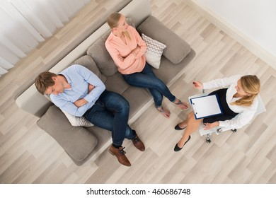 Elevated View Of Unhappy Couple Sitting With Female Psychologist Holding Clipboard At Home