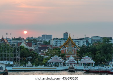 Elevated view of Wat Arun, Temple of Dawn,  complex and wharf with sunset sky on the background. Urban Bangkok scene with Buddhist temple