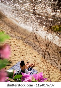 elevated view of woman sitting on beach with clear water and flowers