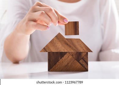 Elevated View Of A Woman's Hand Building House With Wooden Tangram Puzzle Over White Background