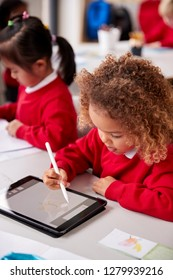Elevated view of young schoolgirl wearing school uniform sitting at desk in an infant school classroom using a tablet computer and stylus, close up, vertical