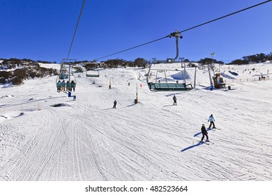 Elevating chair-lift of Perisher valley ski resort at Kosciuszko national park, NSW, Australia. Sunny winter day at high skiing season with exercising people underneath.
