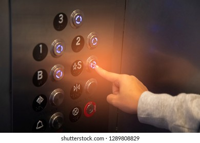Elevator buttons with finger pressing the number s floor, concept of choice