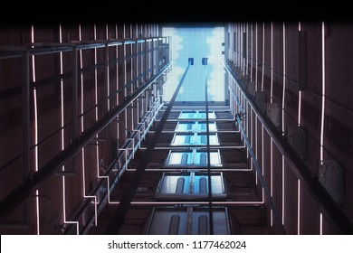 Elevator corridor in the building lit by Blue elumination. Futuristic elevator shaft is located in a high tower. Lift shaft in a residential building. Abstract, background. Bottom view.