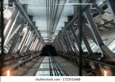 Elevator shaft  interior, view from lift car showing wire rope cables and steel supports with motion blur