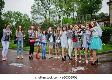 Eleven attractive braidsmaids with lovely bride celebrating bachelorette party with champagne in the park.