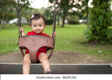 Eleven month old Asian baby girl on a swing